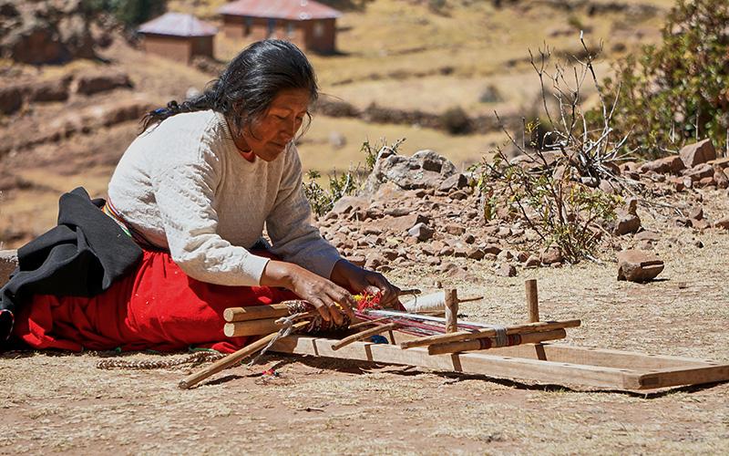 Taquile Island Mujer tejiendo una artesanía de telas